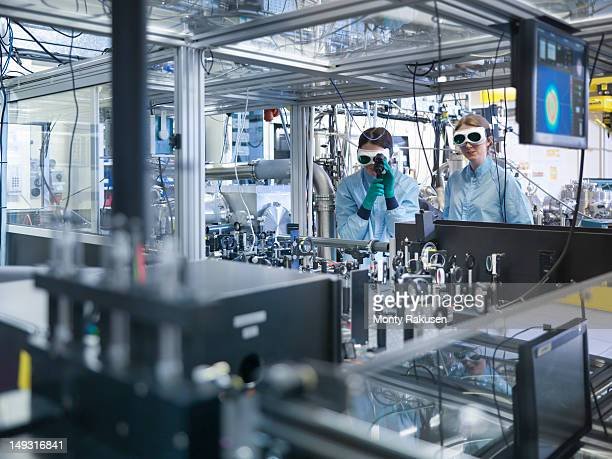 Scientists checking laser beam alignment with an infrared viewer in laboratory