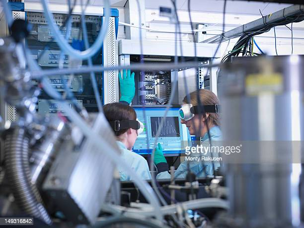 Scientists discussing data of a comb of high harmonics on screen in laboratory