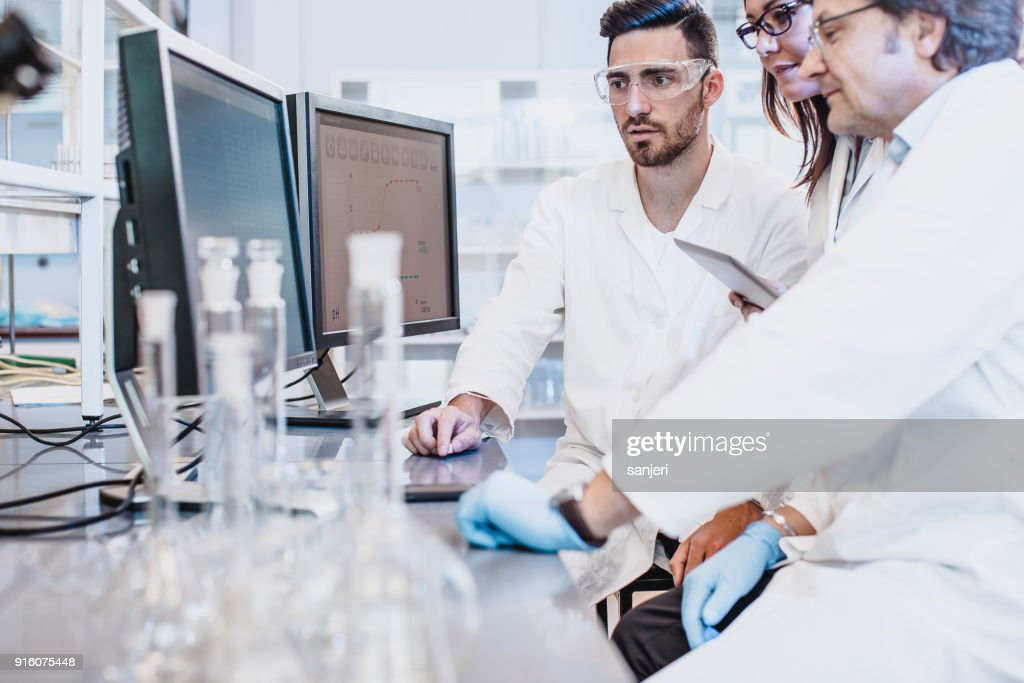 Scientists discussing in the laboratory, using computer : Stock Photo
