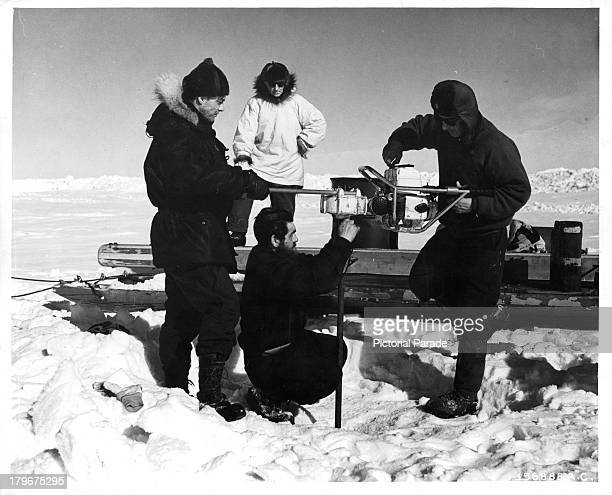 Scientists drill a hole in the huge cake of ice during construction of the Arctic camp site in Greenland
