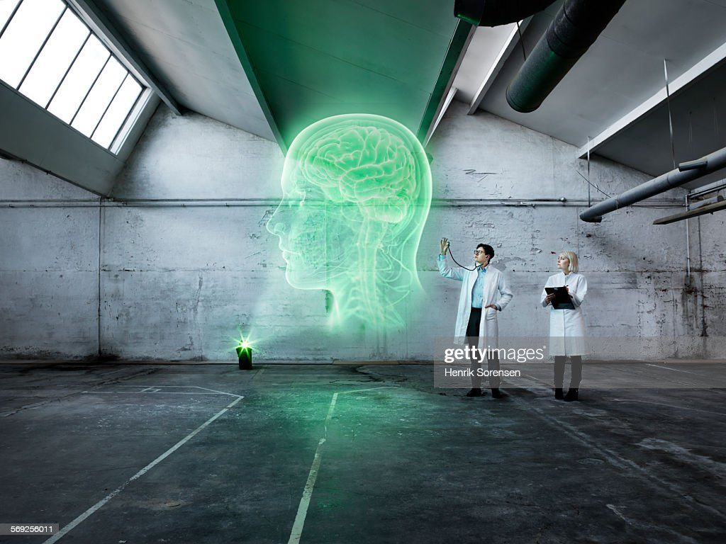 Scientists examining a holographic human head : Stock Photo