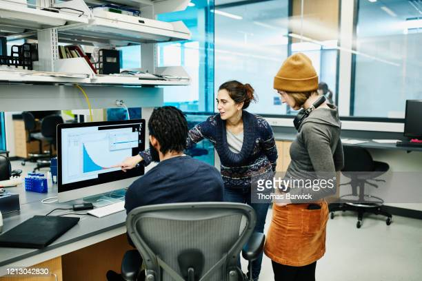 scientists examining data on computer while working in research lab - data stock pictures, royalty-free photos & images