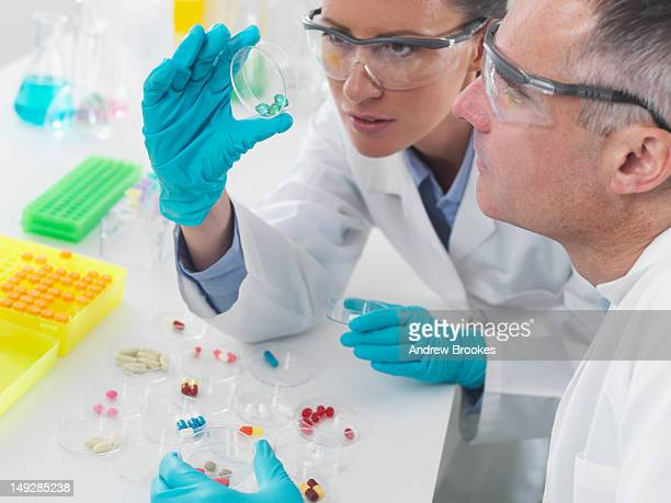 Scientists examining pills in lab