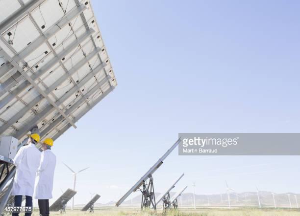 Cientistas examinar painel solar na paisagem rural