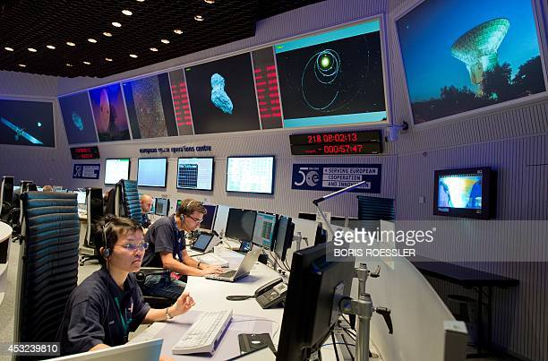 Scientists follow the flight of the Rosetta spacecraft from the control centre of the European Space Agency in Darmstadt western Germany on August 6...