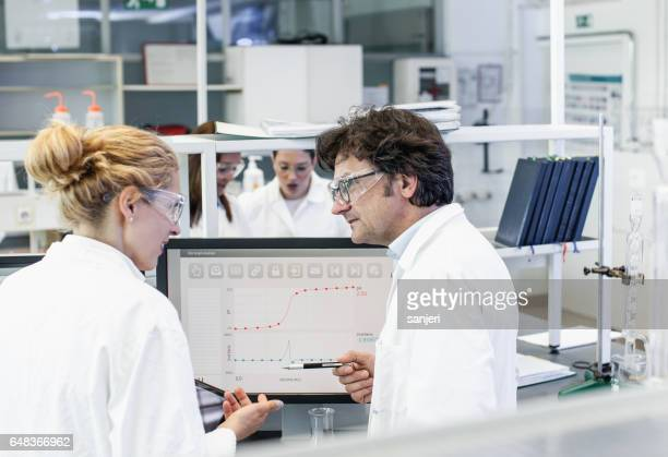 Scientists in a Laboratory Standing Beside Computer Monitors and Discussing