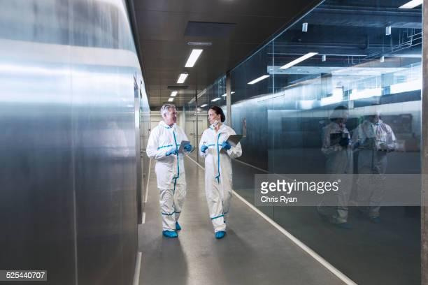 Scientists in clean suits walking in hallway