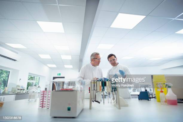 scientists in discussion in laboratory - laboratory stock pictures, royalty-free photos & images