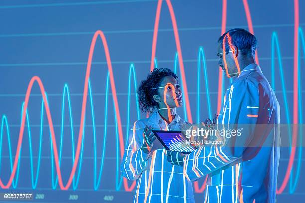 Scientists in discussion with graphical data projection