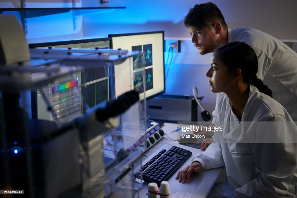 Scientists in laboratory using computer : Stock Photo