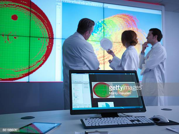 Scientists in meeting in front of graphical display of silicon wafer on screens