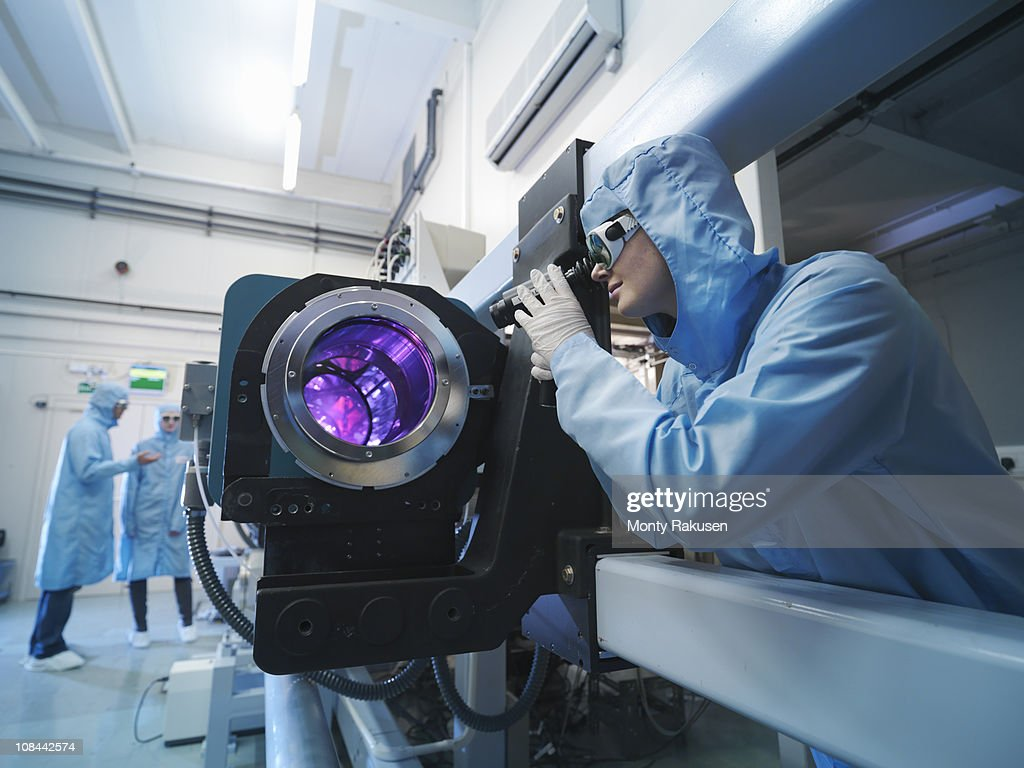 Scientists in protective clothing and goggles in laboratory next to laser equipment : Stock Photo