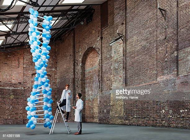 Scientists in warehouse with DNA made of balloons