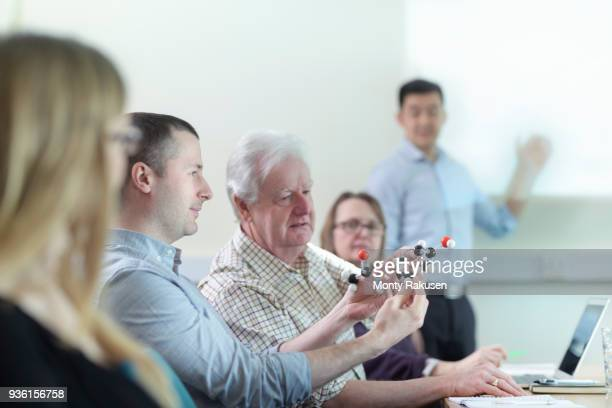 Scientists inspecting Ibuprofen model in meeting room