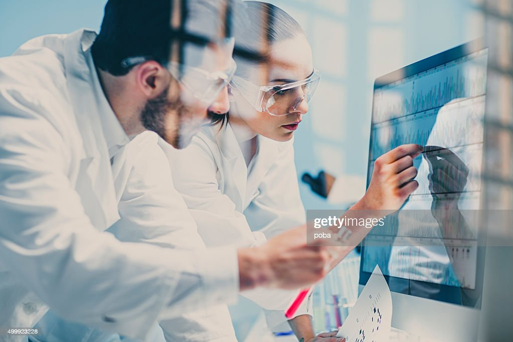 scientists looking at a DNA sequence on the monitor : Stock Photo