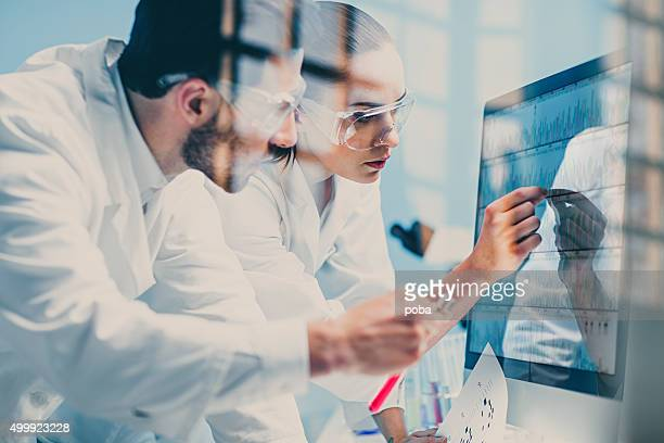 scientists looking at a dna sequence on the monitor - medicinsk forskning bildbanksfoton och bilder