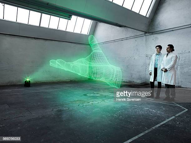 scientists looking at a holographic hand - hologram stock pictures, royalty-free photos & images