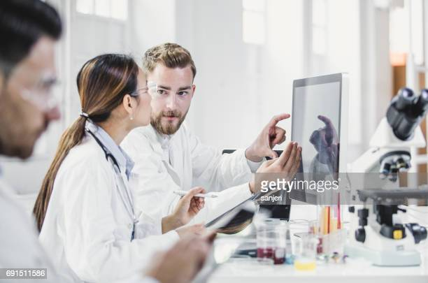 scientists looking at computer monitor and discussing - research stock pictures, royalty-free photos & images
