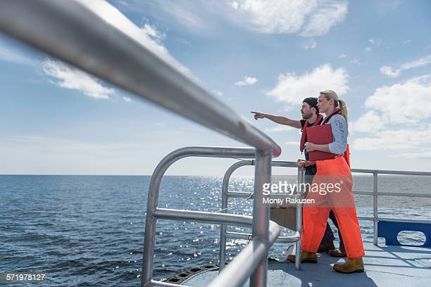 Scientists looking at wildlife on deck of research ship