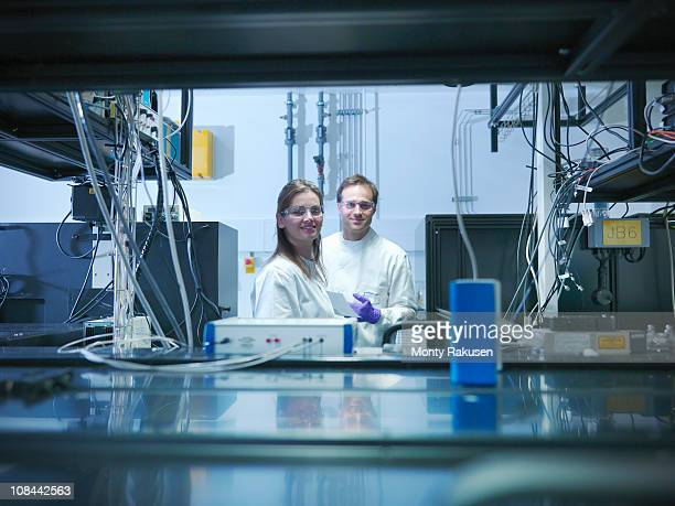 Scientists looking to camera and smiling, in laboratory with laser experiment