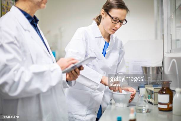 scientists making medicine at pharmacy - homeopathic medicine stock photos and pictures