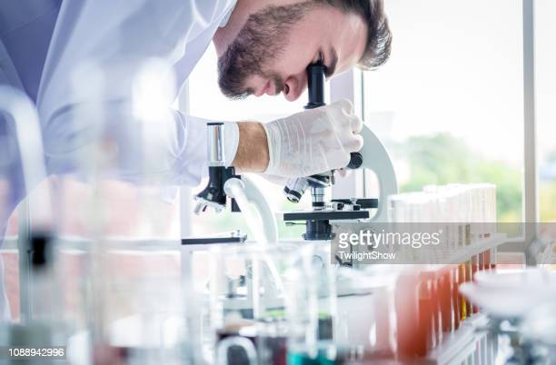 scientists man working and look in to microscope in lab - research stock pictures, royalty-free photos & images