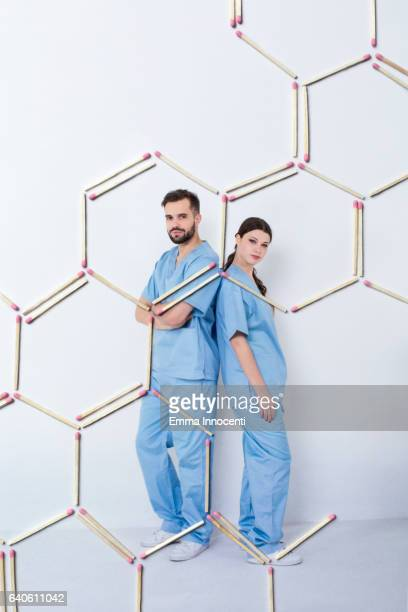 Scientists posing behind a big chemical symbol