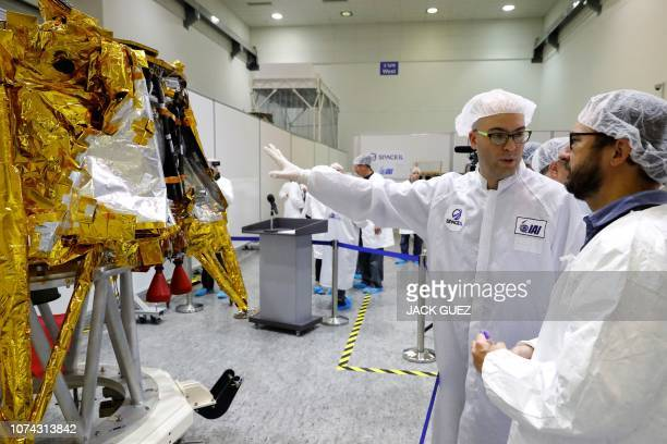 Scientists stand next to a spacecraft weighing some 585 kilogrammes during a presentation by Israeli nonprofit SpaceIL and Israeli stateowned...