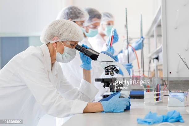 scientists studying a virus ,looking through microscope - research stock pictures, royalty-free photos & images