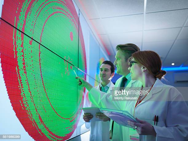 Scientists studying graphical display of silicon wafer on screens
