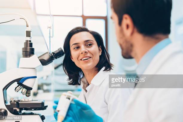 scientists talking in the laboratory - microbiology stock pictures, royalty-free photos & images