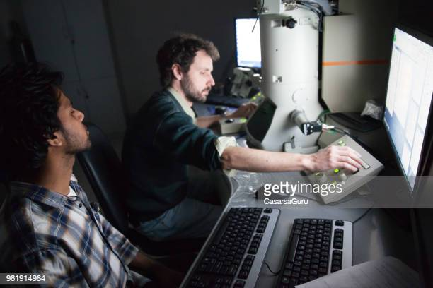 Scientists Using Field Emission Electron Microscope in Laboratory