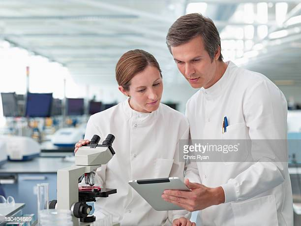 Scientists using tablet computer in lab