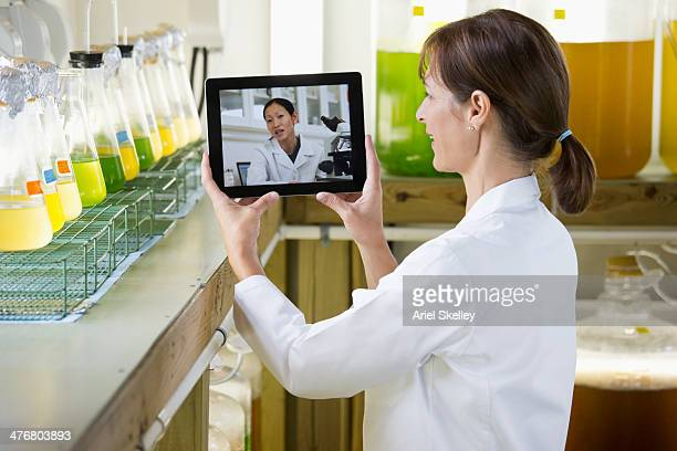 Scientists video conferencing on digital tablet in laboratory