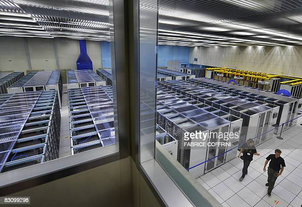 Scientists walk inside the main room at the European Organization for Nuclear Research's Large Hadron Collider Computing Grid computer during its...