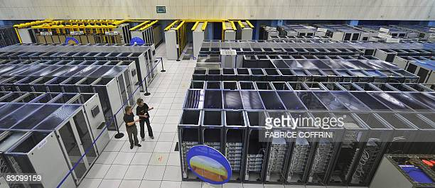 Scientists walk inside the main room of the CERN's LHC Computing Grid computer on its inauguration day on October 3 2008 in Geneva The Worldwide LHC...