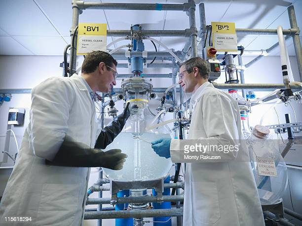 Scientists with laboratory mixing vessel
