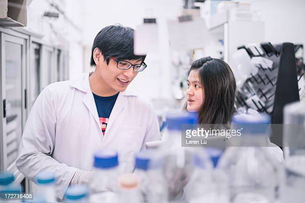 scientists working in cell engineering laboratory - leren stock pictures, royalty-free photos & images