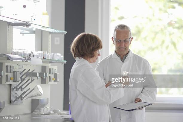 scientists working in laboratory, holding vial - sigrid gombert stock pictures, royalty-free photos & images