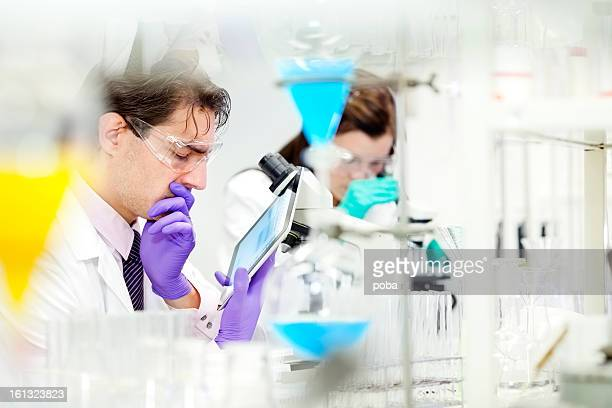 scientists working in  laboratory  using  digital tablet, microscop  and flasks