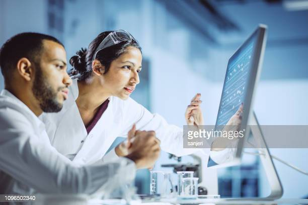 scientists working in the laboratory - ricerca foto e immagini stock
