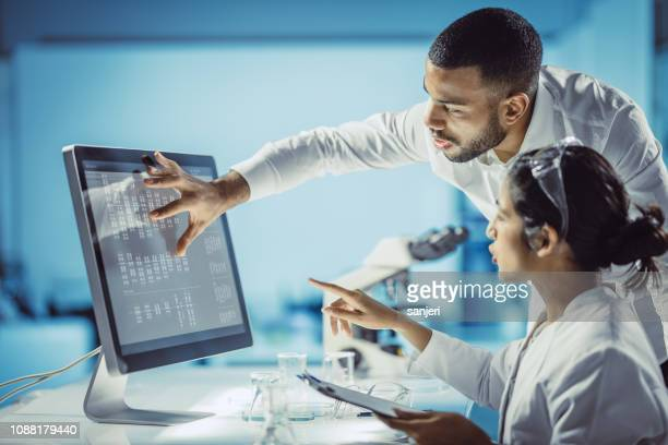 scientists working in the laboratory, using touch screen - chemistry stock pictures, royalty-free photos & images