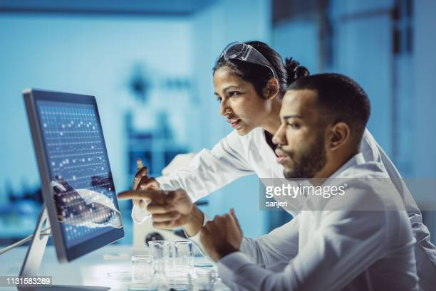 scientists working in the laboratory, using touch screen - biotechnology stock pictures, royalty-free photos & images