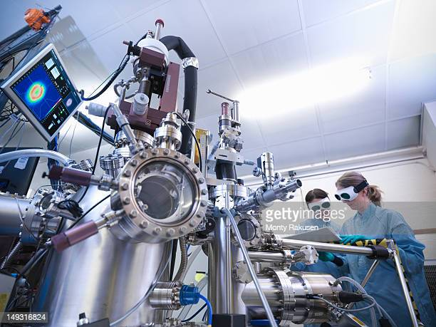 Scientists working together in front of materials science chamber