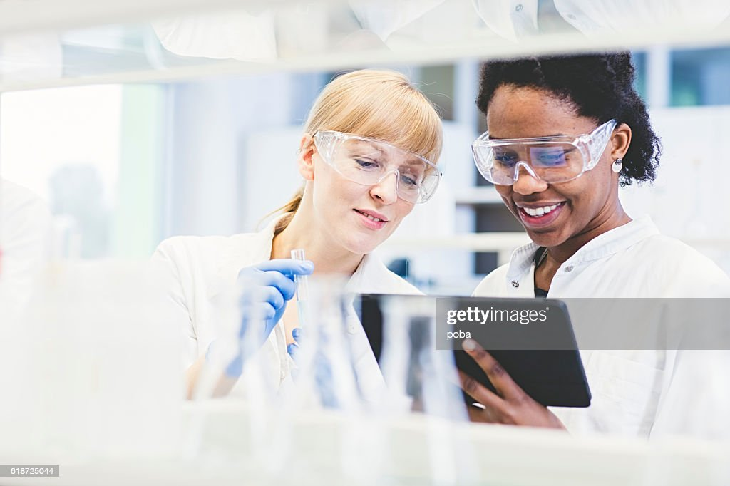 Scientists working together in lab : Stock Photo
