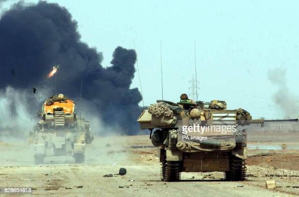 Scimitar of the Queens Dragoon Guards looks on as a striker vehicle also of the QDG fires a sidewinder missile at an Iraqi bunker southern Iraq