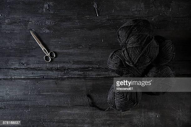 Scissors and balls of black wool on black wood