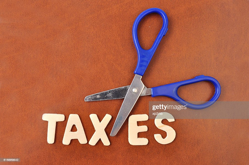 Scissors and the alphabet TAXES : Stock Photo