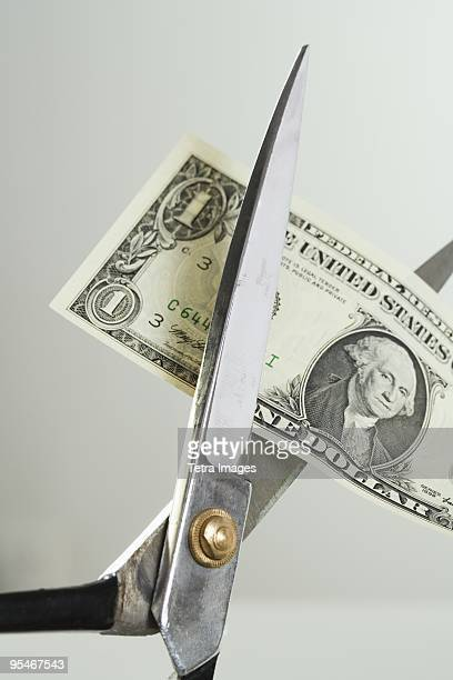 Scissors cutting an American dollar