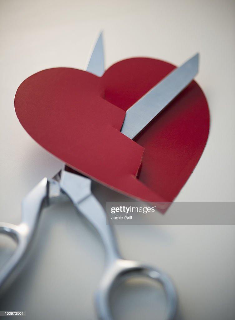 Scissors cutting paper heart : Stock Photo